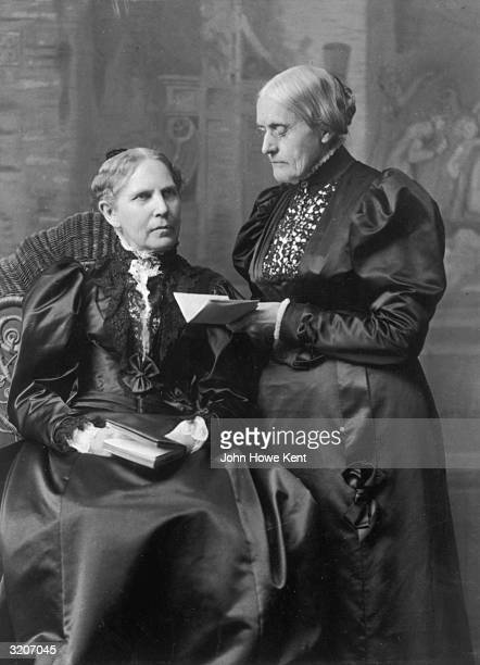 Portrait of American women's rights leader Susan B Anthony and her sister Mary sitting and standing while holding books in front of a painted backdrop