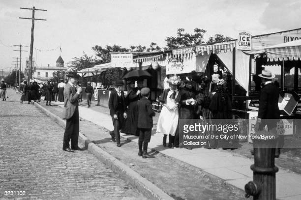 A group of people stand in a line at a frankfurter stand at Audubon Avenue and 193rd Street in the Bronx with Fort George in the background New York...