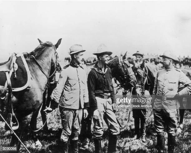 Future American President Theodore Roosevelt stands outdoors in a field with the 1st U.S. Volunteer Cavalry Regiment, known as the 'Rough Riders',...