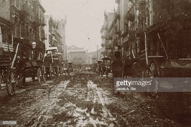 Carriages sit in the mud on either side of Willet Street between Stanton and Houston Street prior to the construction of 'Bone Alley Park,' New York...
