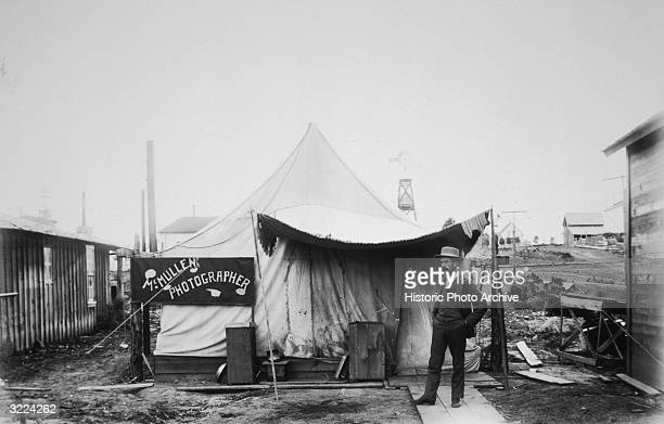 Fulllength image of American photographer John McMullen standing in front of his studio tent on the main street in Burns Oregon This photograph was...