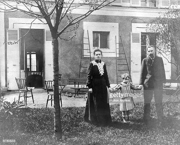 Polishborn physicist Marie Curie and her husband French chemist Pierre Curie hold hands with their daughter Irene in the garden of their home near...