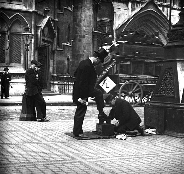 A bootblack at work in a London street.
