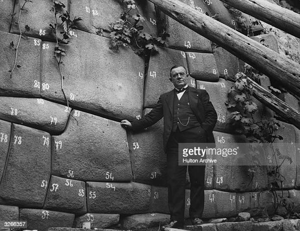 German scientist stands beside the Inca wall he found in Cuzco, Peru. Each stone has been numbered so it can be re-assembled accurately at another...