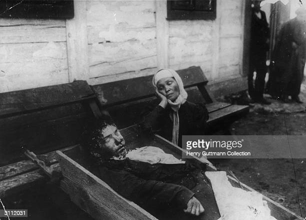 A grieving woman sits by a rough wooden coffin in which is lies the body of a family member the victim of a pogrom