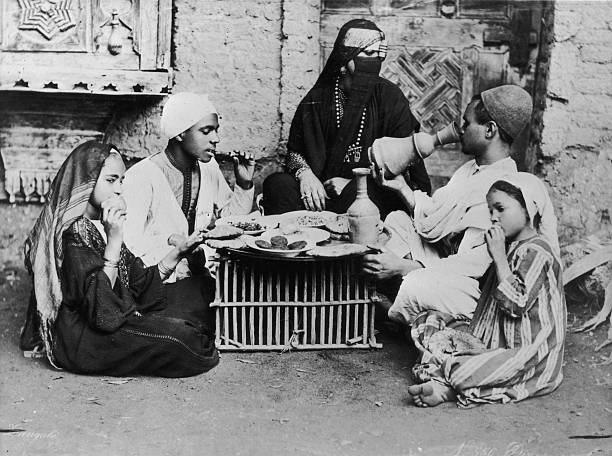 A group of Egyptians sit down to a meal.
