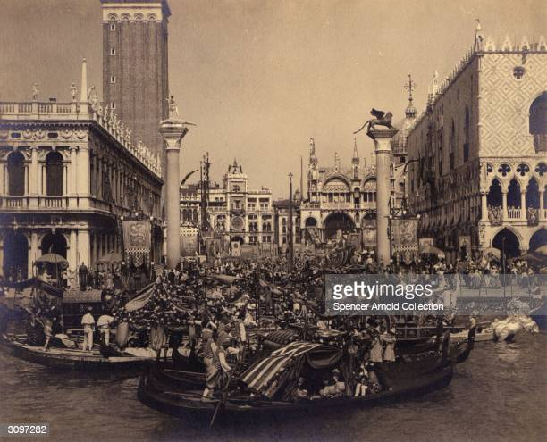 A regatta passes the crowds which have flocked into St Mark's Square in Venice