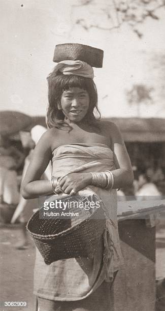 A young woman from Manipur a state in north east India which borders on Burma wears a sarong type garment and carries a basket on her head She has a...