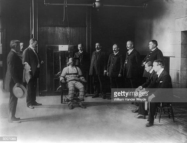 AfricanAmerican man seated in an electric chair surrounded by Caucasian witnesses and guards Sing Sing prison Ossining New York