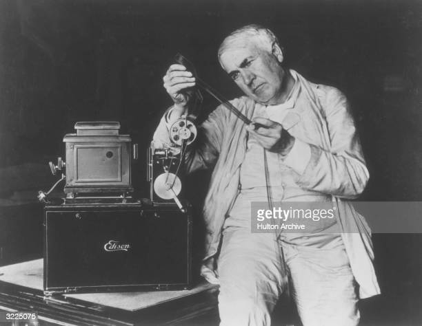 American inventor Thomas Alva Edison examining motion picture film threaded through one of his film projectors