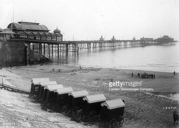 Bathing machines lined up on the beach in front of the North Pier Blackpool