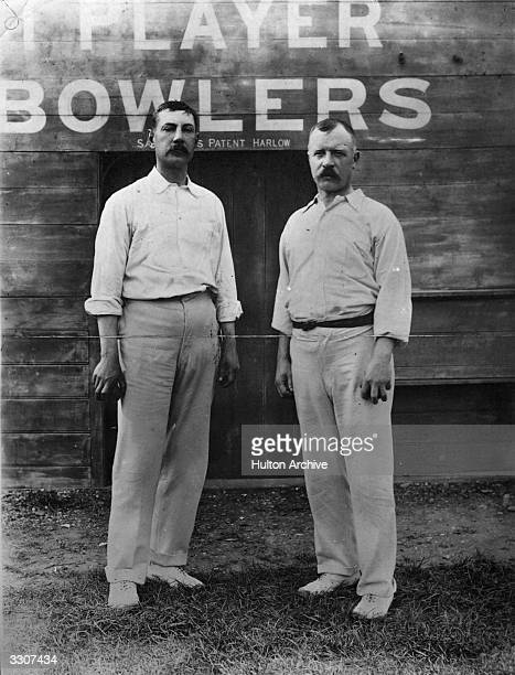 Bill Lockwood, England , Notts and Surrey cricketer, and Bobby Peel, , England and Yorkshire cricketer, in front of the scoreboard.