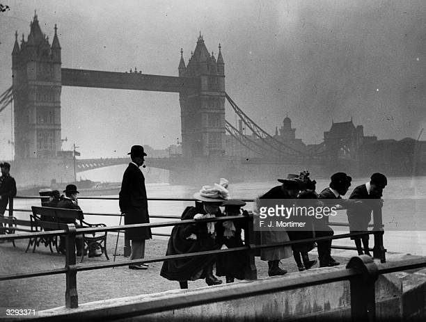 Children peer over the railings by the banks of the Thames with Tower Bridge in the background.