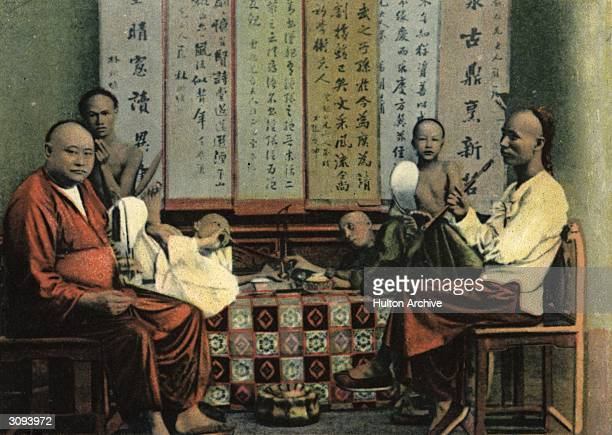 Chinese opium smokers with hookah pipes in Hong Kong.