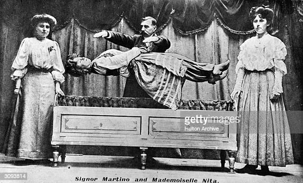Conjuror Signor Martino levitating Mademoiselle Nita during a stage performance