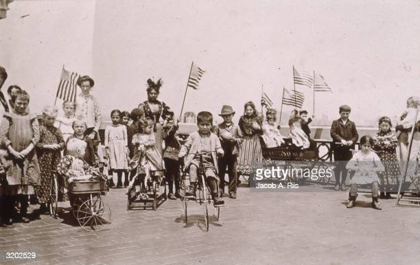Fulllength image of children holding American flags while riding tricycles and wagons in front of women on the rooftop garden of Ellis Island New...