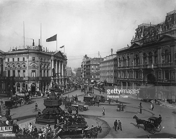 Horse-drawn traffic and passers-by outside The London Pavilion at Piccadilly Circus. The statue of Eros is on the left.
