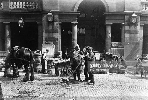 Men sweeping up in Covent Garden fruit and vegetable market London