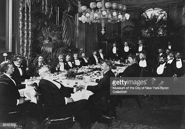 Men wearing formal evening attire and crowns made of holly leaves sitting around a banquet table under a chandelier at a dinner given by or for...