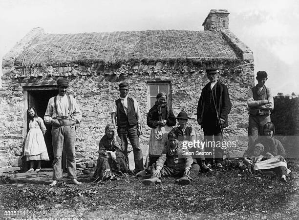 Natives of Gweedore County Donegal outside their thatched smallholding