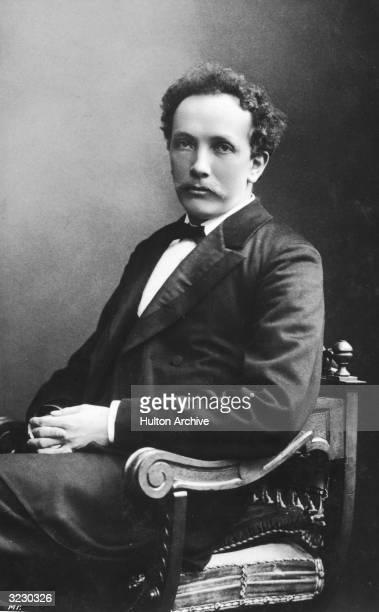 Studio portrait of German composer Richard Strauss sitting in a chair.