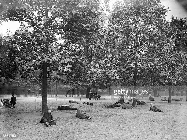 Unemployed men relax under the trees at St James' Park in London.