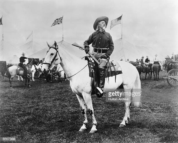 William 'Buffalo Bill' Cody American entertainer sitting on horseback and holding a rifle looks off into the distance as British and American flags...