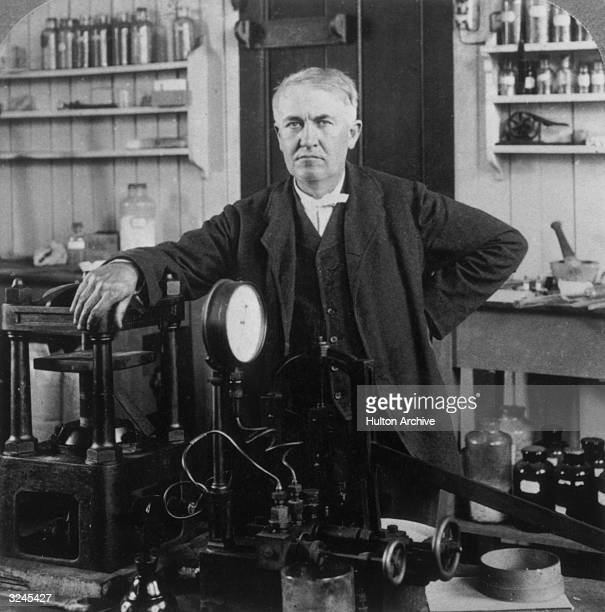 Portrait of American inventor Thomas Alva Edison resting his arm on one of his inventions, in his lab in West Orange, New Jersey.