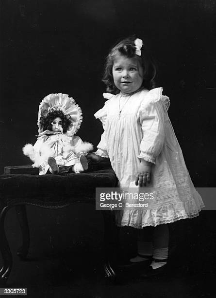 Miss Daniels an Edwardian child stands beside a stool