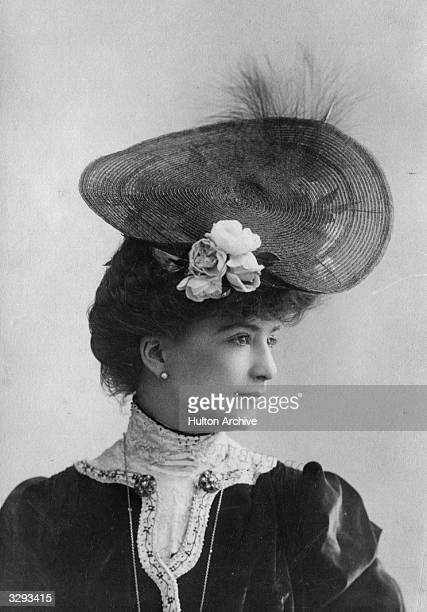 An Edwardian woman wearing a circular hat with flower and feather trimming.