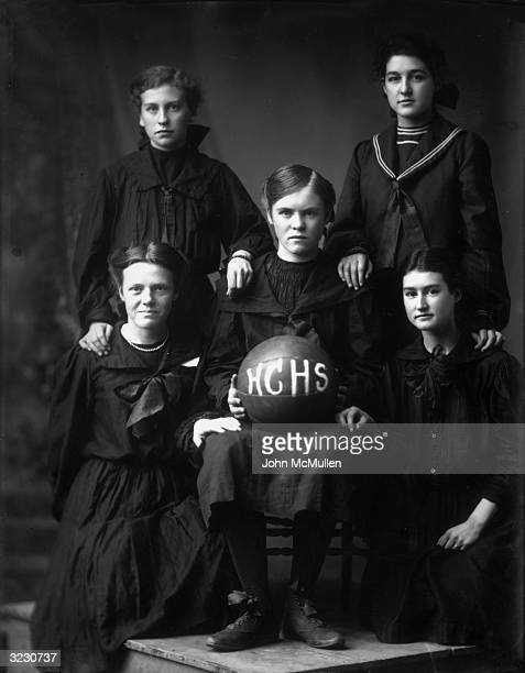 Group studio portrait of five girls on the Harlan County High School women's basketball team wearing dark dresses and holding a basketball with HCHS...