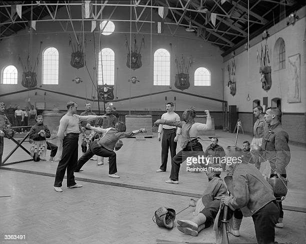 A group of men in an Aldershot gymnasium watch a fencing contest