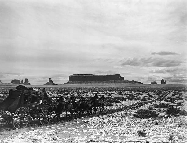 A stagecoach pulled by six horses travels along a dirt...