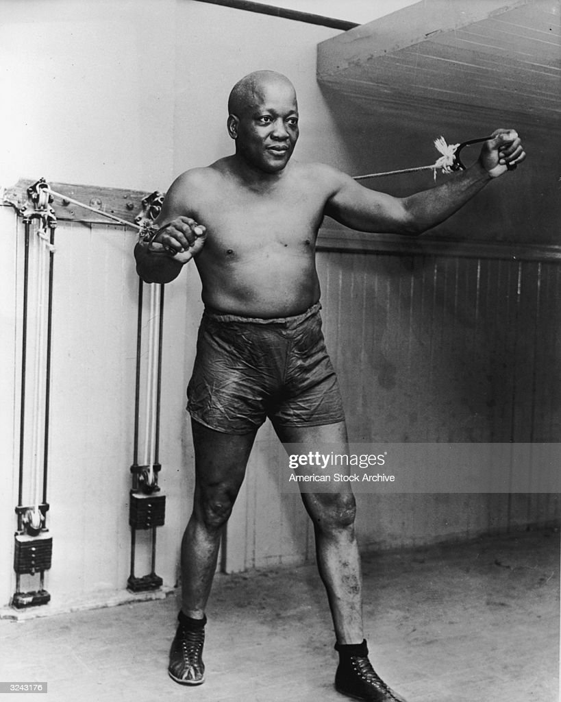 American heavyweight boxing champion Jack Johnson (1878 - 1946) stands and holds two handles as he works out with weights on pulleys.