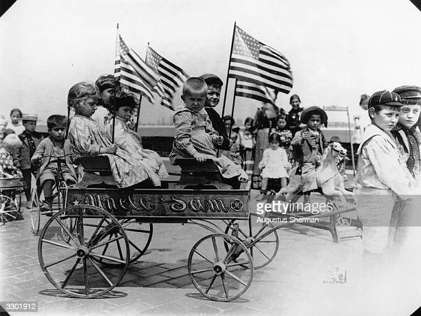 Children playing in a wagon on a roof top playground at Ellis Island Immigration Centre, New York. The wagon has the words 'Uncle Sam' on the side...