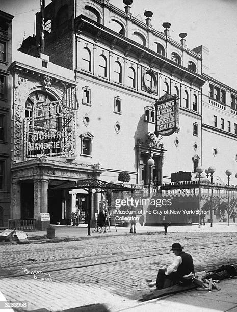 Exterior view of the Lyric and Belasco Theatres on West 44th Street in Times Square New York City A worker sits on the curb in the foreground