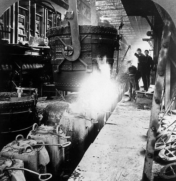 Full-length image of workers in a foundry filling molds...