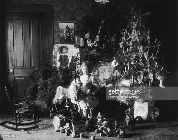 Fulllength portrait of a young girl standing by a Christmas tree a rocking horse and other presents including teddy bears dolls and a jackinthebox...