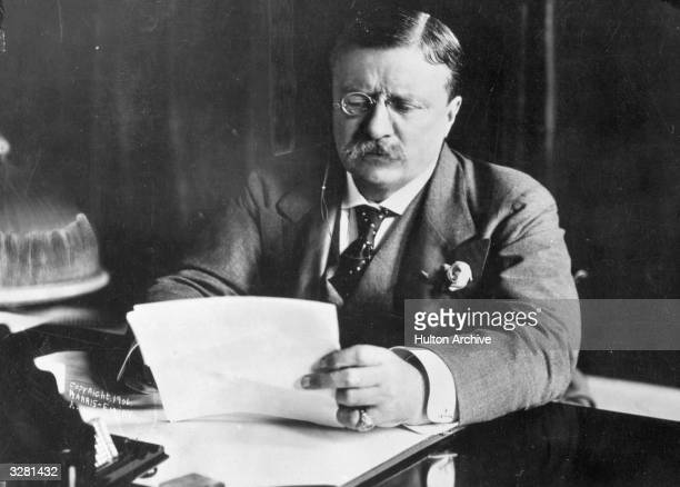 Theodore Roosevelt the 26th President of the United States sitting at his desk working