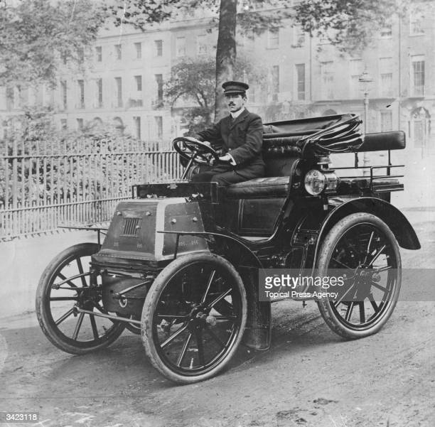 A chauffeur sitting at the wheel of the first car of King Edward VII a 6horsepower Daimler