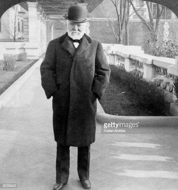 Fulllength portrait of Scottishborn American industrialist and humanitarian Andrew Carnegie wearing an overcoat and hat in the gardens of his home in...