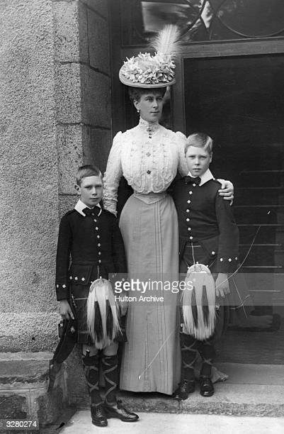 Mary of Teck the wife of George V and Princess of Wales stands at a doorway with her two sons the Duke of Windsor and the future George VI at...