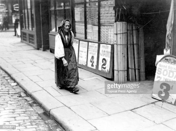 An elderly Italian woman wanders through a shopping area in London.