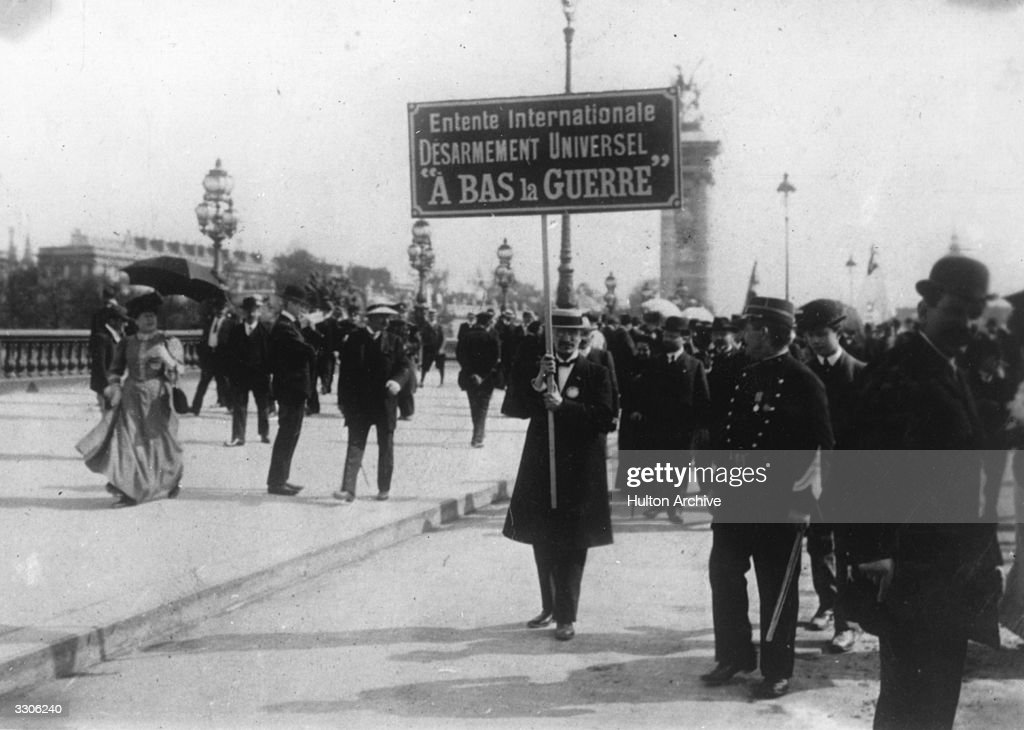 Anti-war demonstrators outside the International Conference at the Hague, 1907. A protestor carries a placard reading ´International Entente, Universal Disarmament, Down With War´.