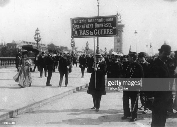 Anti-war demonstrators outside the International Conference at the Hague, 1907. A protestor carries a placard reading ´International Entente,...