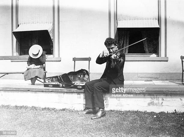 A youth playing the violin while sitting on a wall outsde a house