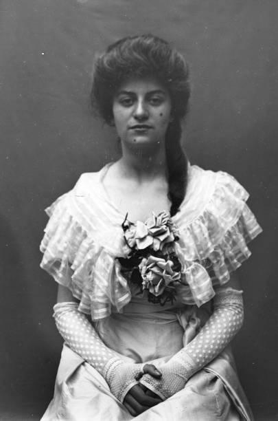 An Edwardian woman wearing three-quarter length lace...