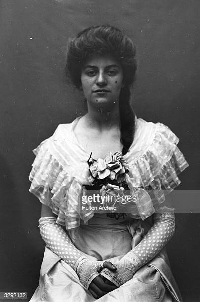 An Edwardian woman wearing three-quarter length lace mittens.