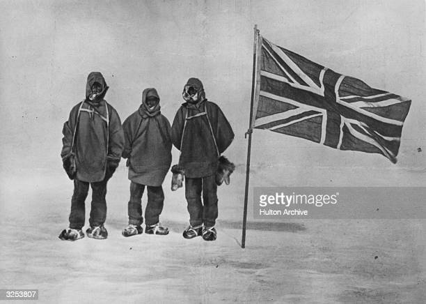 Irish explorer Sir Ernest Henry Shackleton and two members of his expedition team beside a Union Jack within 111 miles of the South Pole a record feat
