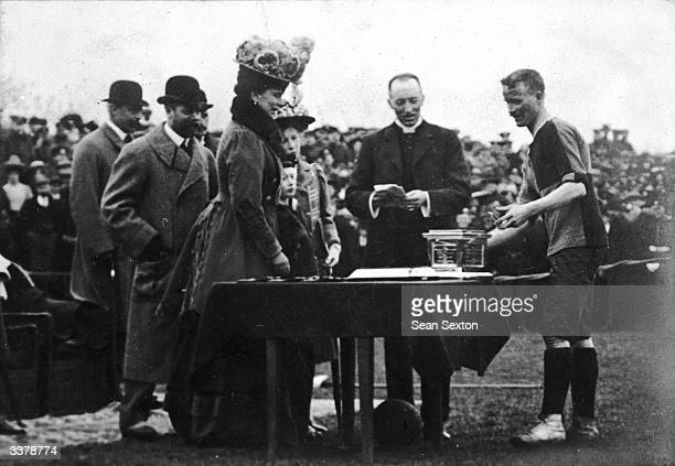The Princess of Wales presents a trophy to the captain of the Royal Irish Rifles football team